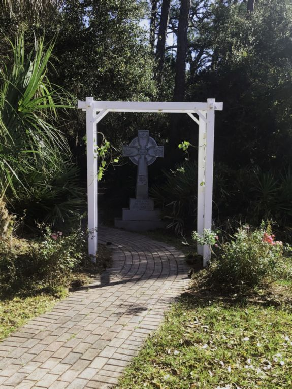 brick walkway with wooden arch